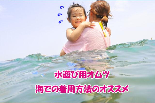 海につかる母と子